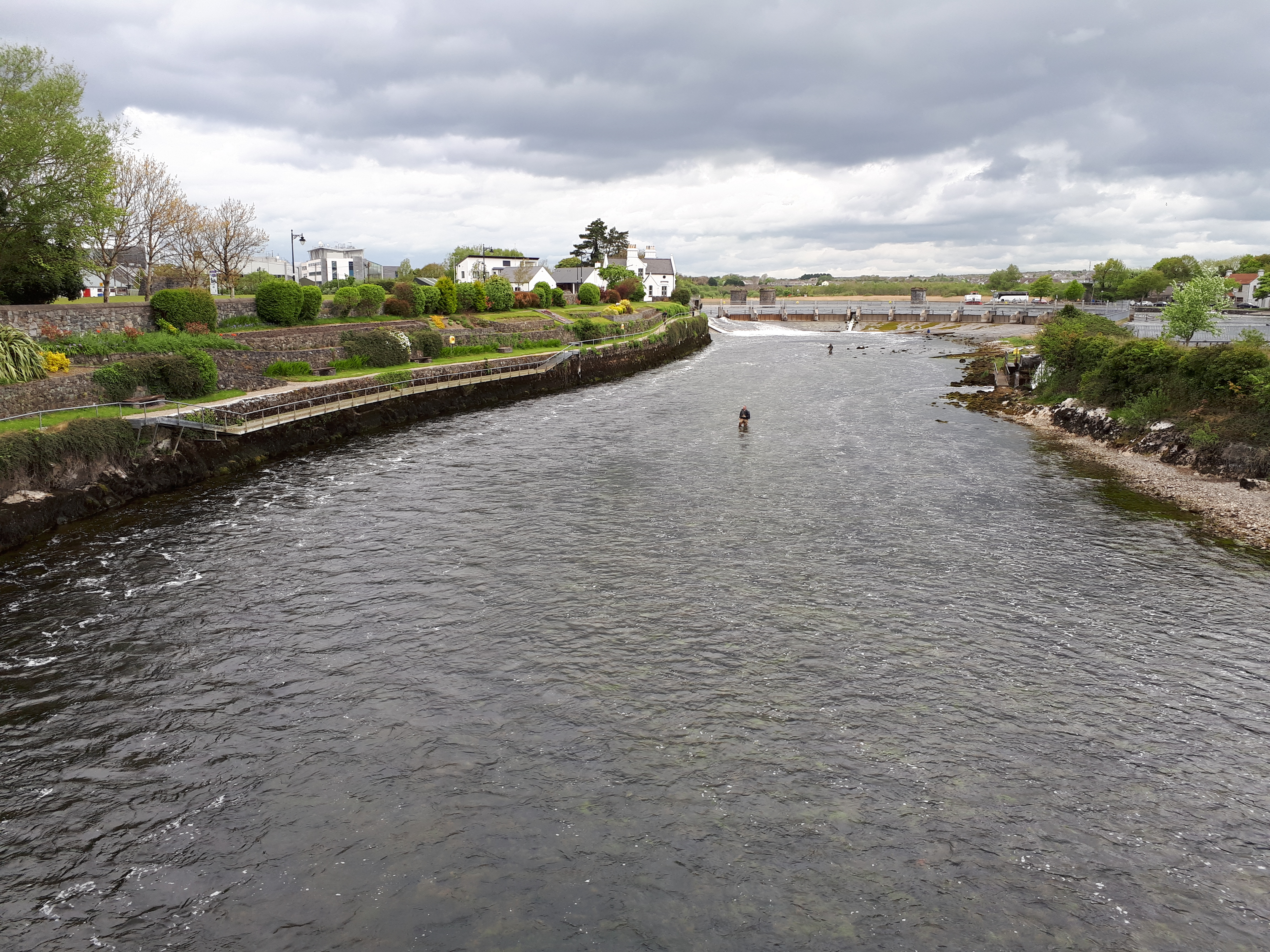 Anglers fishing the fly on a shrunken river Corrib at the Galway Weir